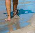 Walk barefoot on the beach young guy is walking bare feet with sea water spray healthy lifestyle sand in summer day Royalty Free Stock Photo
