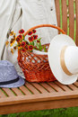 After a walk bench on the grass on the bench white jacket men s and women s hats basket and bunch of flowers Stock Photos