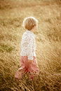 Walk in field little girl walking with dry grass Royalty Free Stock Images