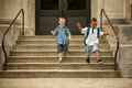 Walk or jump tentative boy watches his adventurous friend leap down the school steps Stock Images