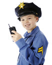Walkie talkie cop closeup image of a happy young boy using his while in his police uniform on a white background Royalty Free Stock Image