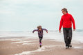Walking along the seacoast dad and cheerful years old girl Stock Image