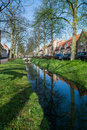 Walking along the small canal in old Dutch village, sunny Sunday Royalty Free Stock Photo