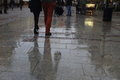 Walking along wet pavement street. Rain in the city. Royalty Free Stock Photo