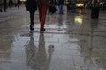 Walking along wet pavement street. Rain in the city. Royalty Free Stock Photo