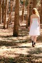 Walking away woman in a forest Royalty Free Stock Image