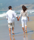 Walking on the beach, wan and woman holding hands. Stock Image