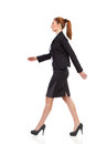 Walking business woman businesswoman in black suit mini skirt and high heels full length studio shot isolated on white side view Royalty Free Stock Photography