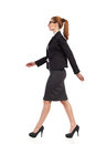 Walking business woman businesswoman in black suit mini skirt and high heels full length studio shot isolated on white side view Royalty Free Stock Image