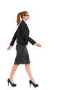 Walking businesswoman side view of smiling and in black suit skirt and high heels full length studio shot isolated on white Royalty Free Stock Photo