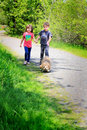 Walking the doggy two little kids a dog on a leash down a country road holding hands shallow depth of field Royalty Free Stock Photos
