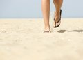 Walking forward in flip flops on beach low angle view of woman feet Stock Photography