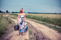 Walking girl with old suitcase on the road Royalty Free Stock Image