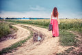 Walking girl with old suitcase on the road Royalty Free Stock Photo
