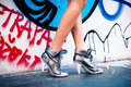 Walking in high heels sneakers woman front graffiti wall Royalty Free Stock Photos