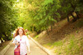 A walking lady an openly smiling along park path with bottle of water cell phone and sunglasses Royalty Free Stock Images