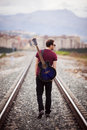 Walking musician young male with his acustic guitar Royalty Free Stock Image