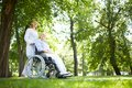 Walking in park pretty nurse with senior patient a wheelchair Royalty Free Stock Image