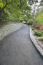 Walking path at crystal springs rhododendron garden asphalt with stone retaining wall Royalty Free Stock Photo