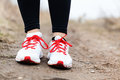 Walking or running legs sport shoes woman and on mountain dirt road adventure fitness and exercising in autumn nature Royalty Free Stock Photography