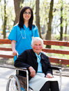 Walking with senior patient in wheelchair kind doctor nurse outdoors taking care of an ill elderly women Stock Photos
