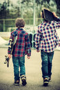 Walking skater boys two towards half pipe vintage effect added Stock Photo