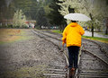 Walking tracks in the rain a lady wet railroad wearing a colorful yellow jacket and carrying an umbrella shallow depth of field Stock Images