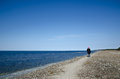 Walking woman along coast a gravel field at springtime Royalty Free Stock Photo