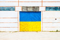 Wall of ancient warehouse with door in ukrainian flag colors - blue and yellow. Ukrainian flag on background of old locked doors Royalty Free Stock Photo