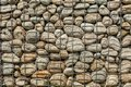 Wall made of round rocks, secured with steel wire net iron ston Royalty Free Stock Photo