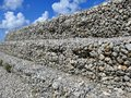 Wall made of round rocks, secured with steel wire net, iron stone gabion