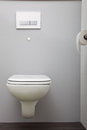 Wall mounted toilet with a concealed cistern close up view of closed in plain white bathroom Stock Photography