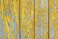Wall of old wooden house with old yellow paint. Peeling paint reveals the wood texture Royalty Free Stock Photo