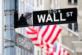 Wall street sign in New York City with american flags on the bac Royalty Free Stock Photo
