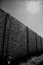 Wall with vanishing point and sun looking down the length of a tall preformed beside a field of grass showing rays lens flare Royalty Free Stock Images