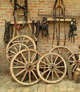Wall with vintage wooden wheels and horse equipmen Royalty Free Stock Image