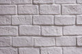 A wall of white brick aging by time and faded by wheather. A stone work and background for house design Royalty Free Stock Photo
