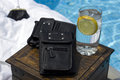 Wallets displayed by the pool resting on a table with a glass of lemonade in the summer Stock Photo