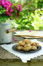 Walnut cookies on garden table sill life with lace doily dog rose bunch in vintage milk can and notebook rusted Royalty Free Stock Photography