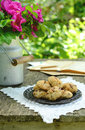 Walnut cookies on garden table sill life with lace doily dog rose bunch in vintage milk can and notebook rusted Royalty Free Stock Photos