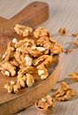 Walnut kernels and whole walnuts on rustic old wooden table Stock Photo