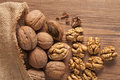 Walnut kernels and whole walnuts on rustic old wooden table Royalty Free Stock Photography