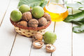Walnut and walnut oil walnuts in bottle on white wooden background selective focus Stock Photos