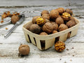 Walnuts with basket on the old wooden table Stock Photo