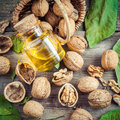 Walnuts, bottle of nut oil and basket on old table Royalty Free Stock Photo