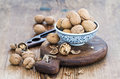 Walnuts in ceramic bowl and on cutting board with nutcracker over  rustic wooden background Royalty Free Stock Photo