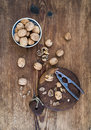 Walnuts in ceramic bowl and on cutting board with nutcracker over  rustic wooden background, top view. Royalty Free Stock Photo