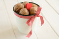 Walnuts in white bucket bounded up in red ribbon Royalty Free Stock Photo