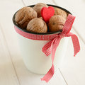 Walnuts in white bucket bounded up in red ribbon and bow cup whote with small heart on wooden background Stock Photos