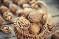 Walnuts in wicker basket on old wooden rustic table selective f closeup focus Stock Images